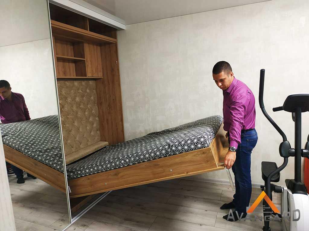 человек складывает кровать